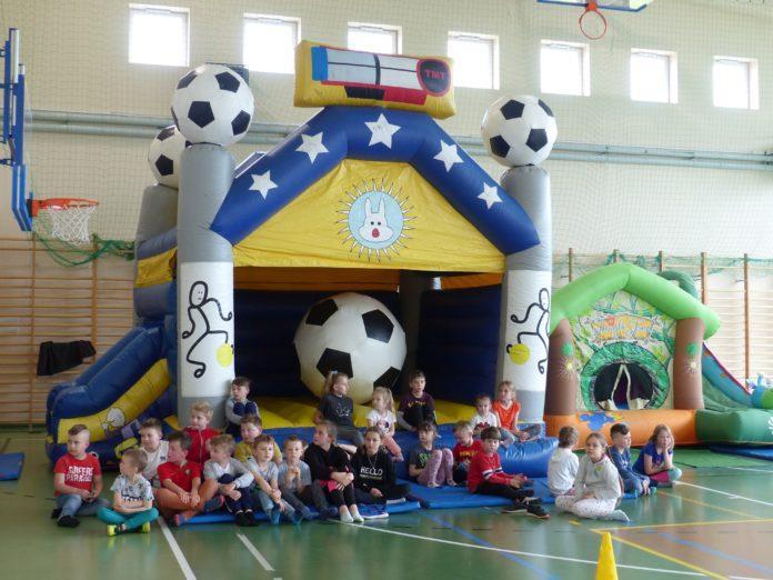 Dzieci uczestniczące w Dniu Dziecka w hali sportowej, przed dmuchańcem z piłką.